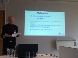 Photo of Steven Marwick giving a presentation at Outcomes based approaches seminar. His lide sayws: Outcomes are about change or difference. So what? Don't happen by themselves - logical result of activity. Realistic and simple (use logic model to link to longer term / more strategic). Outcome > indicator> method