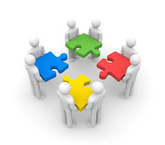Eight people in pairs, each pair holding a large differently coloured jigsaw piece and slotting them together