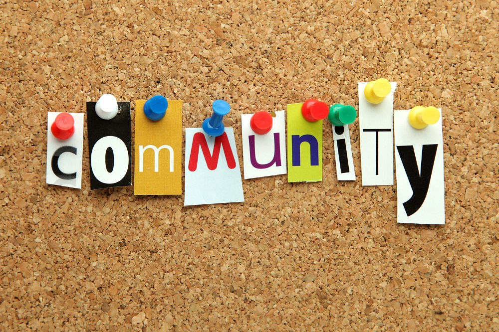 The word community in printed letters pinned on cork noticeboard
